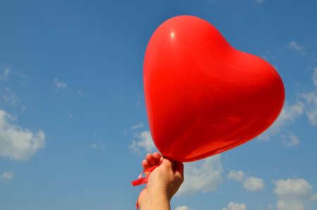 Globo rojo del corazón en el cielo azul con nubes blancas