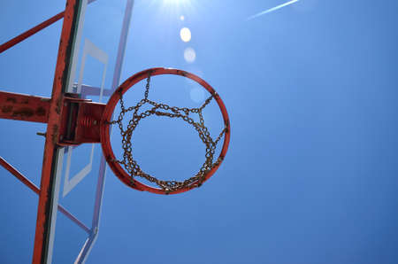 plexiglas: Basketball chain hoop with sunbeams and blue sky as background