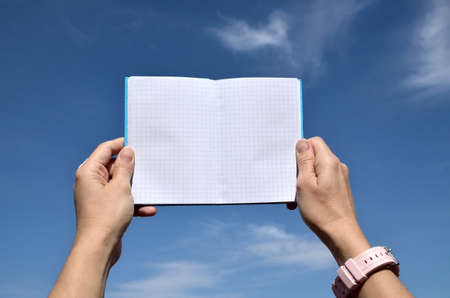 hands on pocket: Pocket notebook with squares pattern held in hands on blue sky as a background