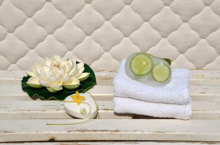 white towels: Milky soap with cucumber slices in ice, artificial lotus and towels on white wooden surface