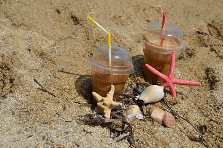 sea grass: Cold coffee frappes set on beach with sea stars, shells and sea grass