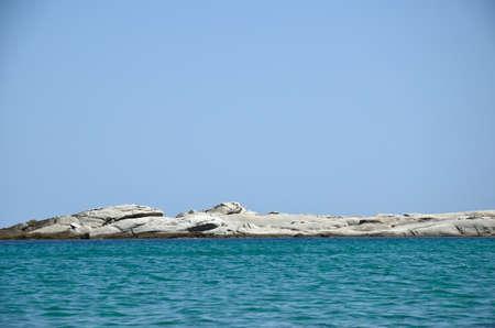 cay: Rocky cay on a horizon between sea and sky