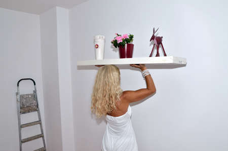 immediately: Lady ready to renew her living room immediately. She is holding heavy unpacked shelf with a vase, flowers and house decoration in caryatid pose.