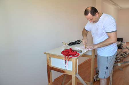 renewing: Man cutting a part of material while renewing his living room