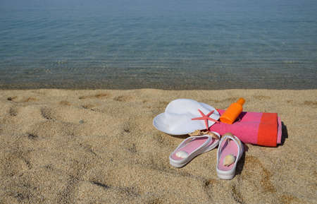 sun lotion: White hat, flip flops, colorful towel, sun lotion, starfish and shells on beach with sea in background