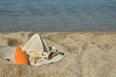 sun lotion: Straw hat, sun lotion, glasses and sea star set on a beach with sea in background Stock Photo
