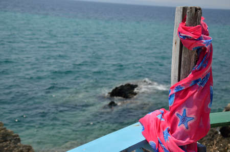 pareo: Pink and blue summer pareo scarf on wooden column over sea