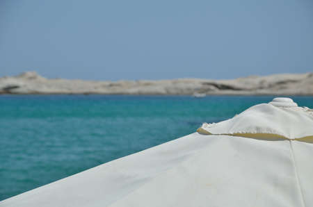 cay: White beach parasol with blurred turquoise sea, blue sky and cay in the distance