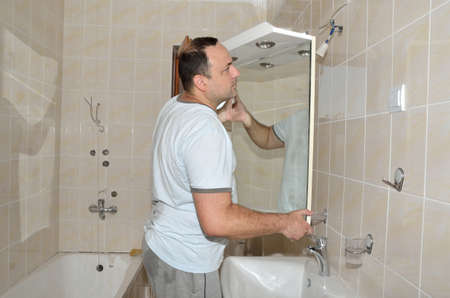 renewed: Man installing a mirror on wall in his renewed bathroom Stock Photo