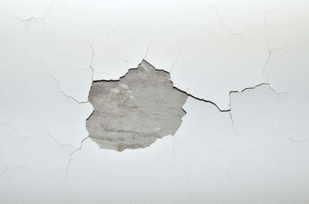 Stucco cracks on ceiling with a concrete place without stucco material