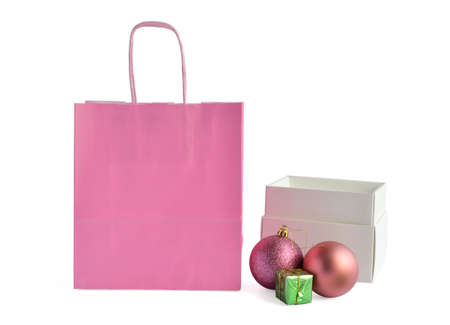 opened bag: Pink paper bag and opened white box with New YearsChristmas tree balls and small decoration gift
