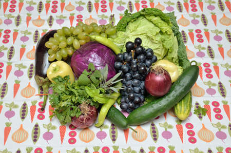 savoy cabbage: Violet and green vegetables and fruits - savoy cabbage, cabbage, onion, pepper, basil, parsley, balm, sage, cucumber, eggplant, red and white grape - on apposite tablecloth
