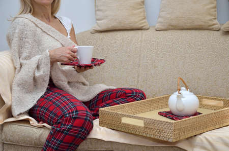 tea cosy: Lady in cosy homewear sitting on sofa and drinking tea