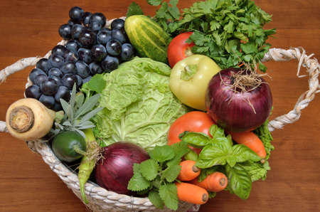 savoy cabbage: White basket with fresh healthy vegetables and fruit - savoy cabbage, red onion, tomato, pepper, basil, parsley, balm, sage, cucumber, carrot and grape on wooden surface