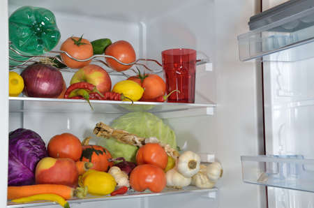 filled: Different fruits, vegetables and water on refrigerator shelves Stock Photo
