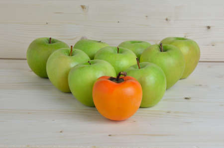 outcast: Triangle of green apples with kaki apple in front of others Stock Photo