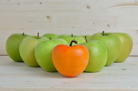 Triangle of green apples with kaki apple in front of others Stock Photo