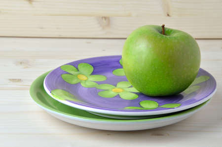 porcelain flower: Green apple on vintage violet porcelain plate with flower pattern