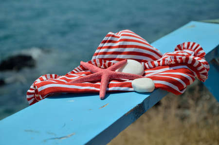 red pebble: Red-white bikini with red sea star and white beach stones on blue wooden beach bench with a sea in background