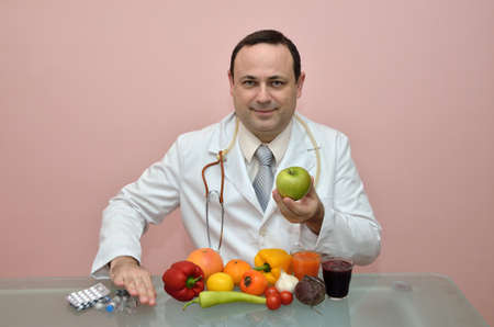 recommending: Doctor recommending fresh green apple and other colorful, healthy food and pushing away pharmaceutical products