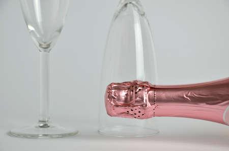 bottleneck: Pink champagne bottleneck with two glasses in background