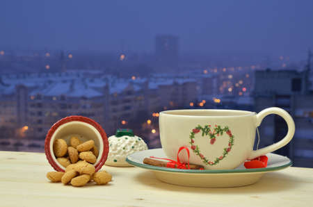 window view: Evening tea of cinnamon flavor with amaretti biscuits in fine crockery set by the window with view on residential city area
