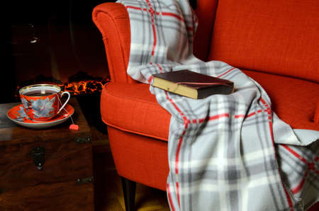 Soft blanket and book on elegant armchair, a cup of hot tea beside it and fireplace in background