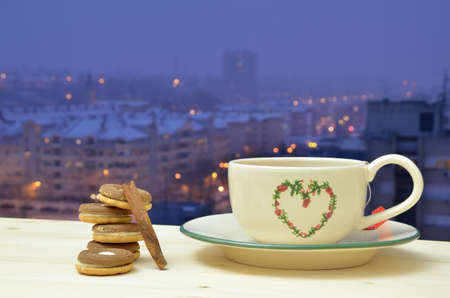 window view: Cup of evening wintry tea of cinnamon flavor with chocolate cookies by the window with view on residential city area Stock Photo