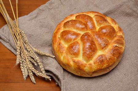 sacco juta: Pane fatto domestico fresco sul sacco di iuta con il mazzo di spighe di grano secco