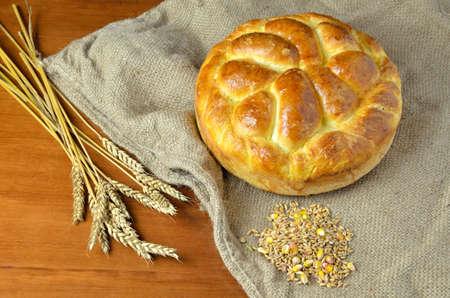 sacco juta: fresca fatta in casa insieme pane sul sacco di iuta con il mazzo di spighe di grano e cereali secchi