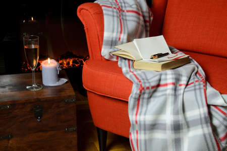 Soft blanket, book, notepad and pen on elegant armchair, a glass of wine and candle beside it and fireplace in background