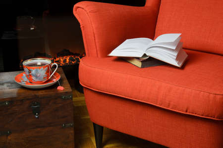 tea cosy: Books on elegant armchair, a cup of hot tea beside it and fireplace in background Stock Photo