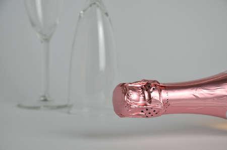 bottleneck: Pink champagne bottleneck with two champagne glasses in background