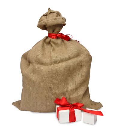sacco juta: sacco di iuta con nastro rosso e scatole regalo accanto, su sfondo bianco Archivio Fotografico