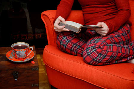 homeware: Lady sitting in an armchair in cozy homeware, reading a book and drinking tea by the fireplace Stock Photo