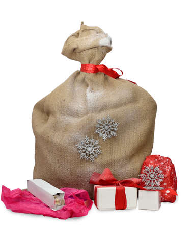 jute sack: Jute sack tied with red ribbon, gift boxes and opened presents beside, on white background