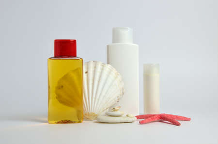 cosmetic product: Bottles of lady body and face cosmetics with sea symbols as shells, starfish and pebbles