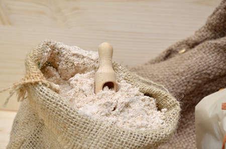 sacco juta: Sacco di iuta di farina di grano intero con il cucchiaio di legno d'epoca Archivio Fotografico