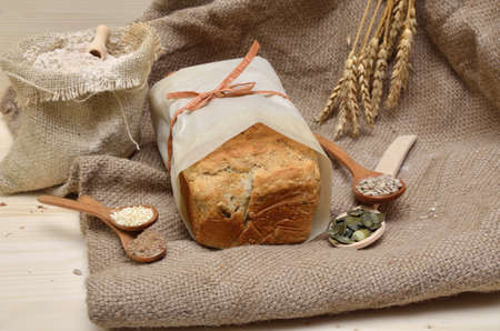 whole grain: Loaf of homemade whole grain bread with pumpkin, flax, sunflower and sesame seeds on jute cloth with sack of whole grain flour Stock Photo