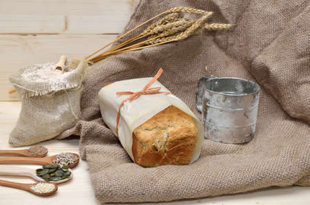 sifter: Domestic whole grain bread with pumpkin, flax, sunflower and sesame seeds on jute cloth with sack of whole grain flour and sifter