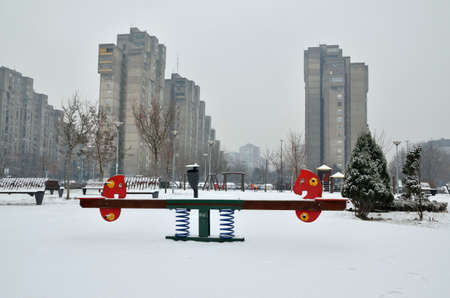 see saw: Seesaw on playground covered with snow with skyscrapers in background