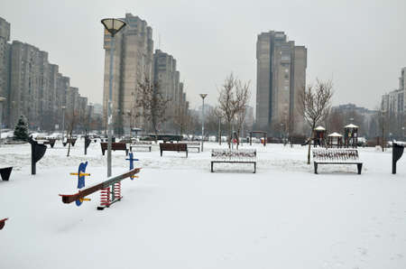 see saw: Seesaw on the playground of a city park covered with snow with skyscrapers in background