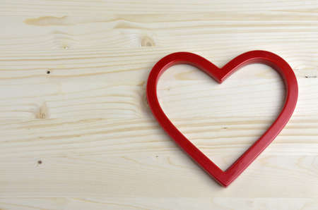 plastic heart: Red plastic heart shape on wooden background