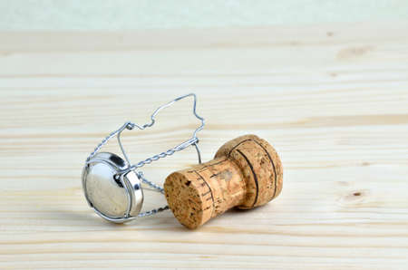 uncork: Cork and wire retaining frame and cap on wooden table Stock Photo