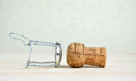 uncork: Champagne cork and wire cap on wooden table