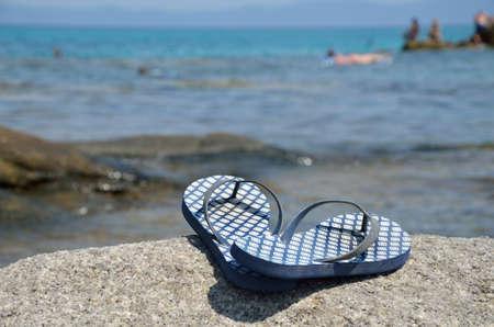 flipflops: Blue flip-flops on the beach by the sea