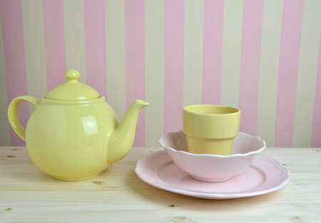 yellow tea pot: Yellow pot and cup with pink plate and bowl on kitchen table and pink-yellow wall in background