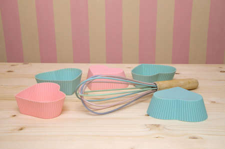 egg whisk: Pink and blue muffin liners and egg whisk on wooden kitchen table with pink-yellow wall in background