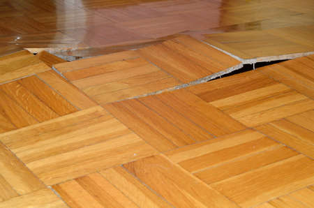 Damage of wooden floor. Parquet lifted up under influence of destructive elements. Stockfoto