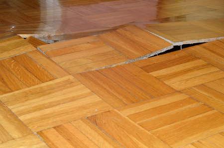 El daño del suelo de madera. Parquet levantado bajo la influencia de los elementos destructivos. Foto de archivo
